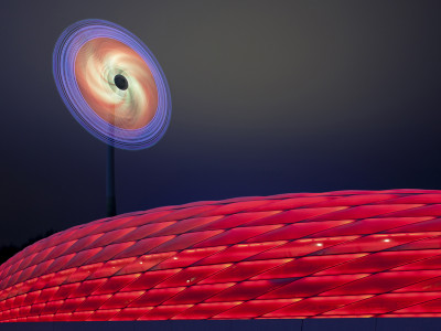 The wind turbine next to Allianz-Arena as an illuminated complete work of art